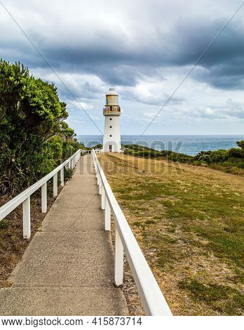 The path to the lighthouse is fenced with a railing. The Great Ocean Road runs along the Pacific coast of Australia. Magnificent snow-white lighthouse on the ocean shore.
