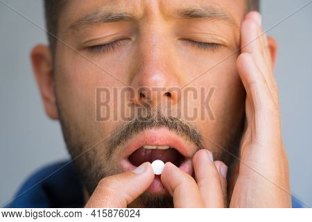 Man Suffering From Headache. Painkillers To Relieve Pain. Close Up Of Man Face Holding Temple And Ta