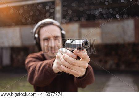 A Man Shoots A Gun, Aiming At The Target. A Man Wearing Protective Headphones. A Wall And A Roof Wit