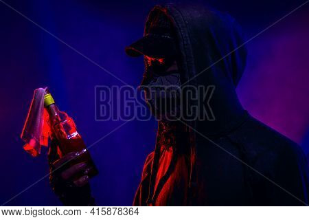 Rebel With Molotov Cocktail Posing Over Dark Background
