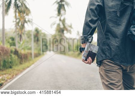 Rear View Of Man With Backpack Hold Passport And Map Hiking And Walking On The Road In Forest. Backp