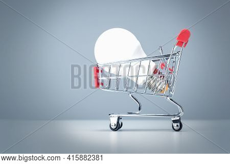 Light Bulb In The Shopping Cart On Blue Background. Energy Supplier To Save Money Concept.