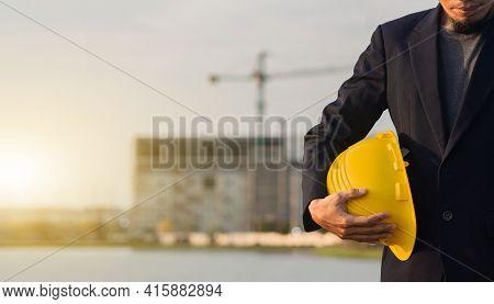 Businessman Holding Yellow Helmet Standing Outdoor Area Site Construction , Engineer Worker  Hard Ha