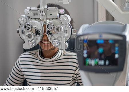 Close-up Of African Teen Girl Doing Eye Test On Phoropter, African Teen Girl Checking On Her Eye Wit