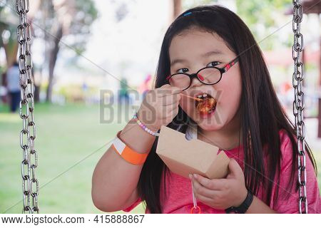 Child Is Sitting And Eating From A Paper Plate. Girl Eats Lunch On A Swing In The Shade. Children We