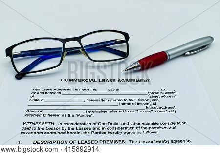 Model Of Commercial Lease Agreement On A White Table, With Glasses And Pen