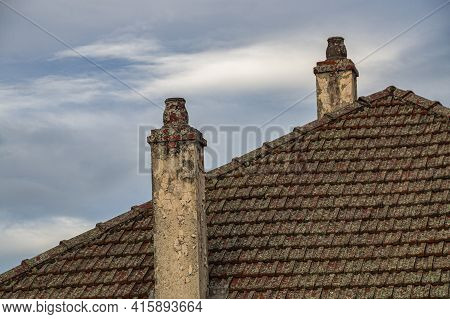 Old Dilipidated Chimney Pots On Tiled Roof In Bad Condition