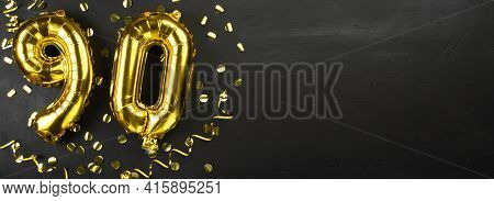 Golden Foil Balloon Number Ninety. Birthday Or Anniversary Card With The Inscription 90. Black Concr