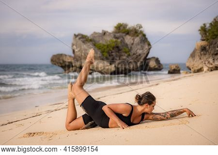 Yoga Bali. Caucasian Woman Practicing Salabhasana Variation B, Stag Locust Pose On The Beach. Outdoo