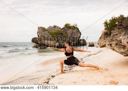 Bali Beach Yoga. Caucasian Woman Practicing Virabhadrasana Ii, Warrior Ii Pose. Strong Body. Healthy