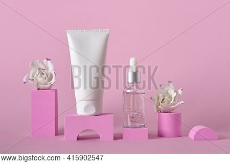 Beauty Natural Skincare Product Mock Up. Cream Tube, Serum Bottle And Flowers On Different Geometric