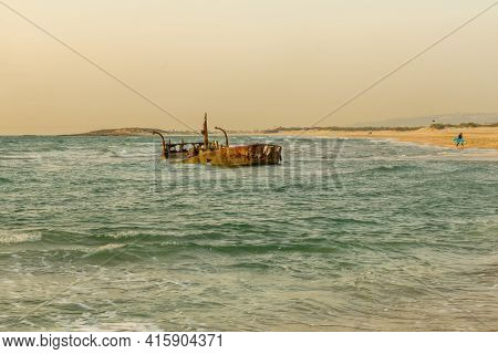 Sunset View Of A Rusty Shipwreck In Habonim Beach, Northern Israel