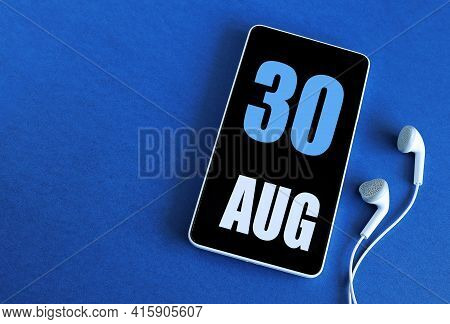 August 30. 30 St Day Of The Month, Calendar Date. Smartphone And White Headphones On A Blue Backgrou
