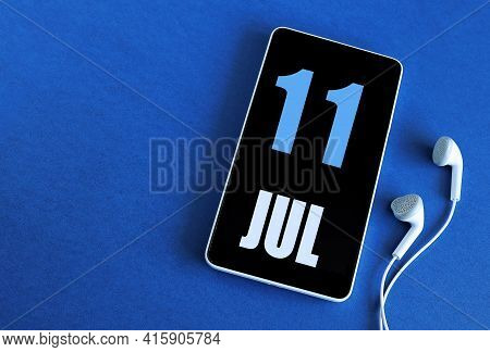 July 11. 11 St Day Of The Month, Calendar Date. Smartphone And White Headphones On A Blue Background