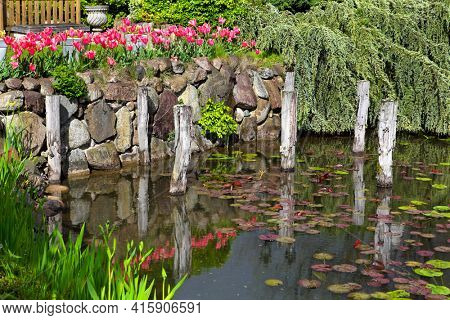 Small garden pond with stone shores and many flowers and decorative vegetation