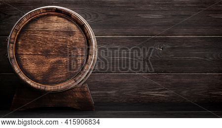 Old wooden barrel for wine or whiskey aging. In front of wooden wall with copy space