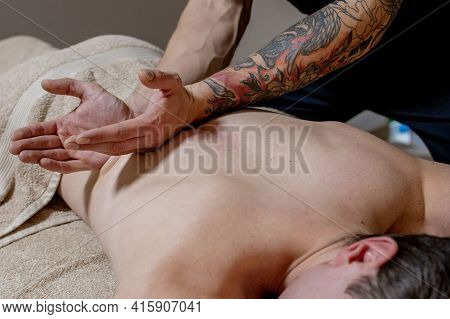 Young Man Enjoying Relaxing Body Massage In Spa Salon Or Massage Room. Qualified Specialist Massagin