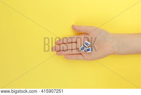 A Woman's Hand Holds Three Dice. A Game Of Dice With Numbers. Board Game Items. Yellow Background.
