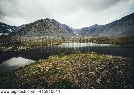 Scenic Mountain Landscape With Glacial Lake Among Mountains Under Gray Cloudy Sky. Atmospheric Alpin