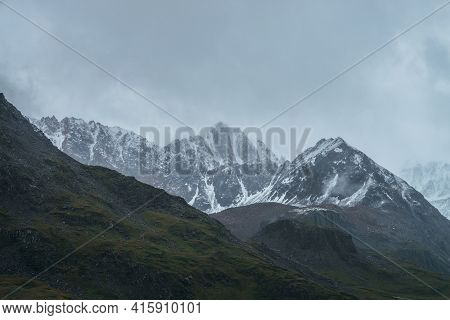 Atmospheric Alpine Landscape With Great Mountain Peaked Top With Snow In Low Clouds. Dramatic Mounta