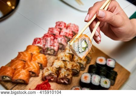 Girl Holding Chopsticks Sushi Roll On The Background Of A Set Of Various Sushi Rolls. Close-up, Sele