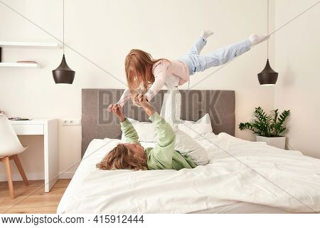Brother And Sister Having Fun On The Bed. Boy Is Holding His Sister On His Legs White Furniture And