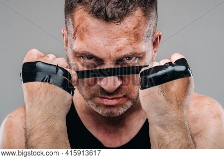 On A Gray Background Stands A Battered Man In A Black T Shirt Looking Like A Fighter And Preparing F