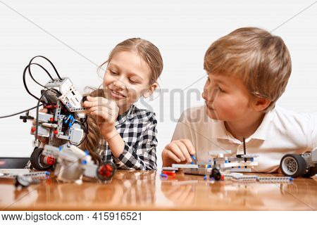 Front View Of Kids Having Fun, Creating Toys. Science Engineering. Nice Interested Friends Smiling,
