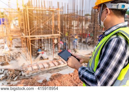 Construction Civil Engineer Or Architect With Hardhat On Construction Site Checking Schedule And Bui
