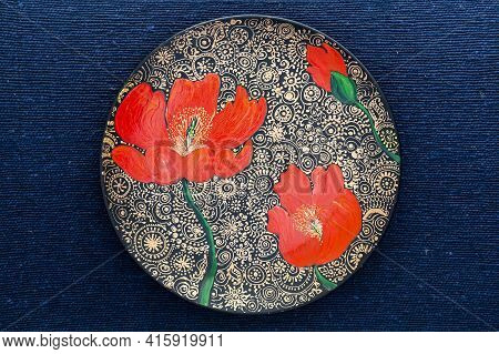 Decorative Ceramic Plate With Red Poppies, Painted Plate On A Blue Fabric Background, Close-up, Top
