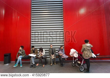 Shanghai, China, April 2: Group Of Chinese People Sitting Down On A Red Bench At The New Modern Art