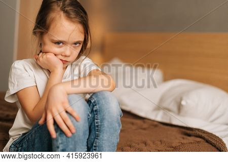 Close-up Face Of Frowning Beautiful Little Girl With Wet Eyes From Tears Sits On Bed In Bedroom And