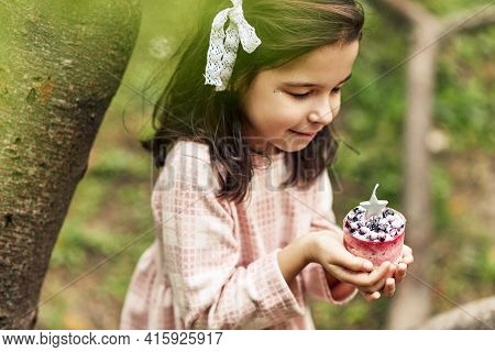 The Portrait Of A Beautiful Little Girl With Closed Eyes Makes A Wish With The Birthday Cupcake In T