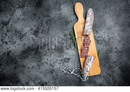 Traditional Spanish Fuet Thin Dried Sausage With Sliceson The Wooden Board. Top View