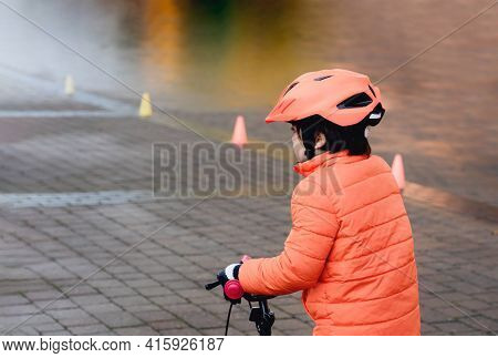 School Kid Learns To Ride A Bike In The Park, Outdoor Portrait Of A Young Boy On Bicycle,  Child In