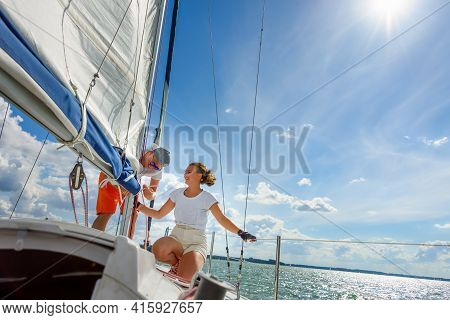 Young Man And Woman Sailing On A Yacht. Female Sailboat Crewmember Trimming Main Sail During Sail On