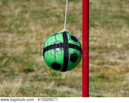 Tetherball Totem Ball Attached To A Red Metal Pole With Grass In The Background And Space For Graphi