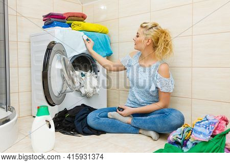 Woman In Bathroom Sorting Different Colored Clothes Laundry For Washing In Machine, Using Detergent
