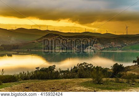 Andalucia Sunset Landscape With Wind Turbines On Hills. Lake Embalse Del Guadalhorce, Ardales Reserv