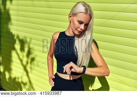 Fit Young Woman Checking Progress After Workout Exercises On Smart Watch Standing Against Green Wall