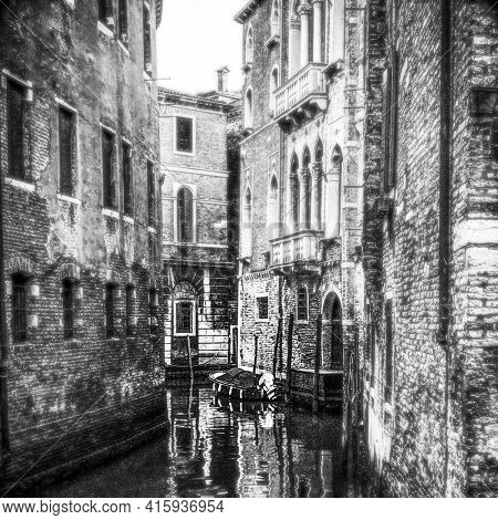Black and white view of a small canal in Venice a boat is docking