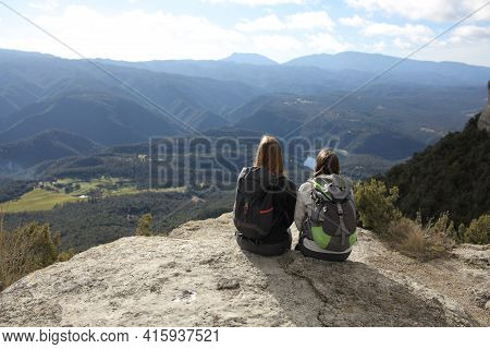 Back View Portrait Of Two Trekkers Resting Contemplating Views On The Top Of A Cliff In The Mountain