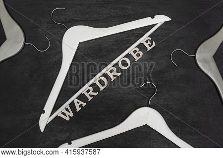White Hangers And Wardrobe Inscription On Black Background. New Clothes
