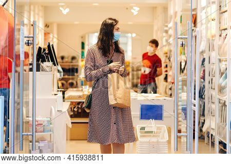 Woman Wearing Safety Face Mask During Shopping Time. Young Female With Shopping Bags In The Mall. Fa