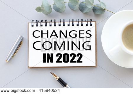 Change Is Coming In 2022. Text On White Notepad Paper. Near Cups With Coffee And Plants On A Gray Ba