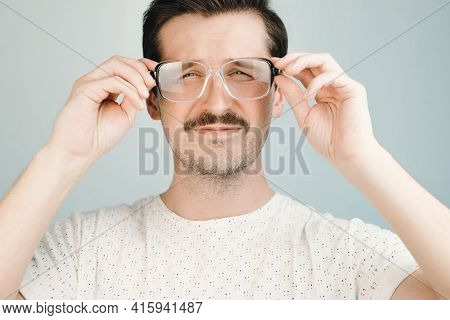 Young Man In Big Glasses Squints At The Camera, Close-up. Health Problem Concept, Low Vision, Glasse