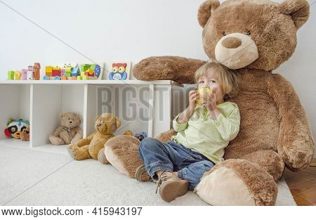 Cute Happy Child Boy Sitting On His Giant Teddy Bear And Eating A Fresh Yellow Apple Fruit. Children