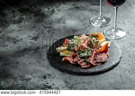 Italian Antipasti Wine Snacks Set. Cheese Variety, Antipasto Platter And Wine In Glasses Over Black