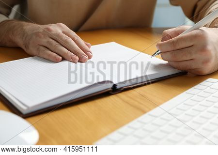 Left-handed Man Writing In Notebook At Wooden Desk, Closeup