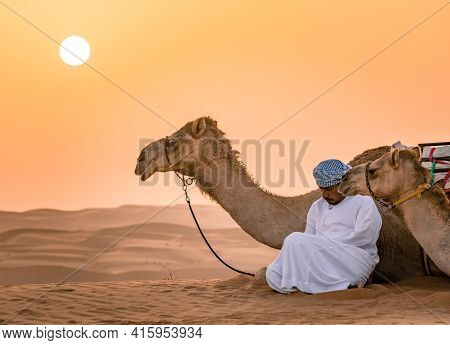 Wahiba Sands,oman - 04.07.2018: A Man In White Robe And His Camel Sit On The Desert Sand.